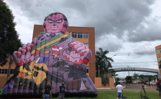 IMAGEM: Manifestantes erguem boneco inflável de Bolsonaro em frente à Anvisa
